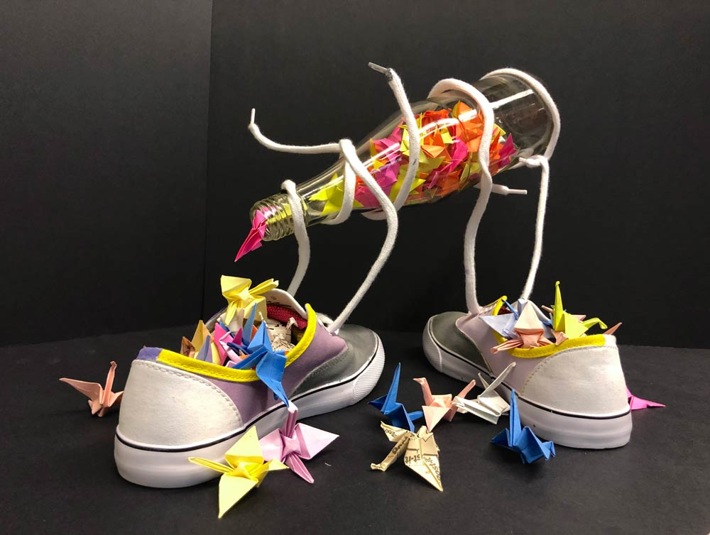 Pair of sneakers filled with colored pieces of construction paper with the shoestrings holding up a tilted glass soda bottle also filled with construction paper