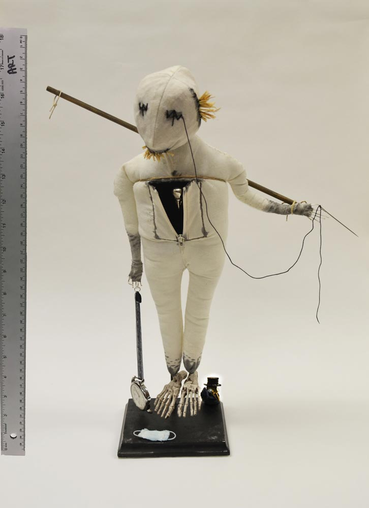 White stuffed doll dragging a clock in one hand and holding a stick in the other behind its back