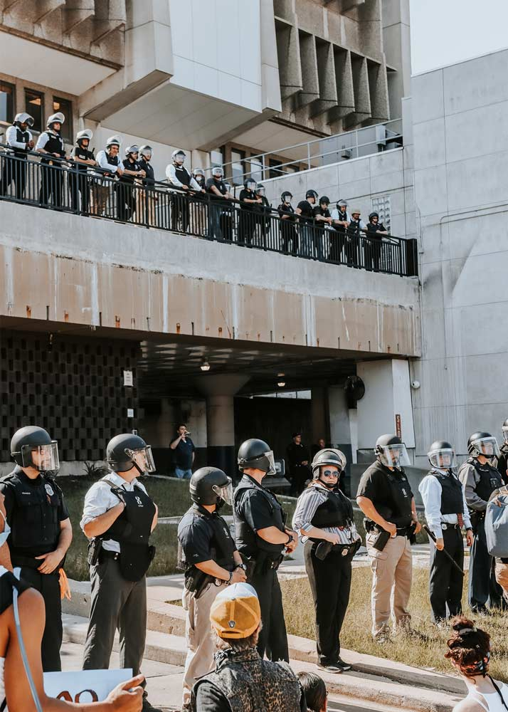 Wall of police officers in helmets and bulletproof jackets in front of a building