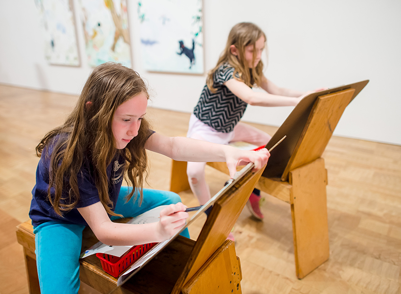 Two young girls working on easels in the Museum